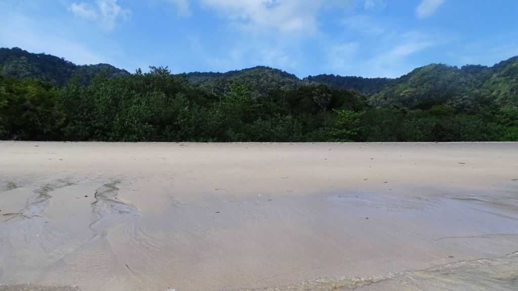 bamboo bay beach in koh lanta with greeneries and hills in the background