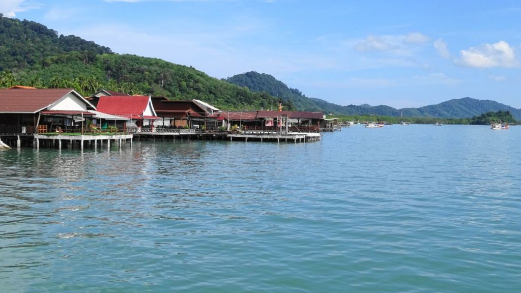 stilt restaurants at the sea shore with hills in the background in Old lanta, Thailand