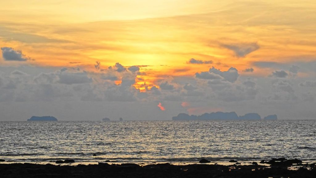 Sunset on Klong Khong beach in Koh Lanta, rocks in the sea in the foreground, tiny rocky islets on the horizon