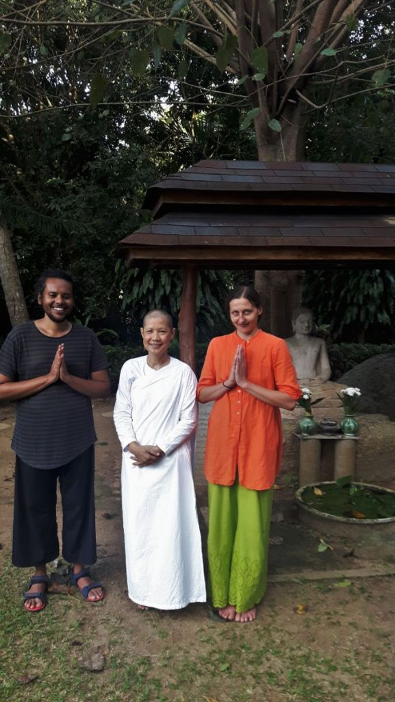 Weronika and Sayak with their meditation teacher dressed in white at the retreat centre