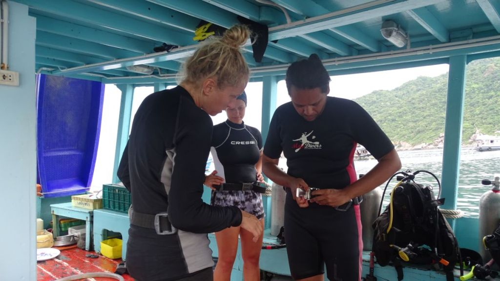 Sayak is fixing his weight belt on the boat with help of the instructor before the dive in Koh Tao, Thailand