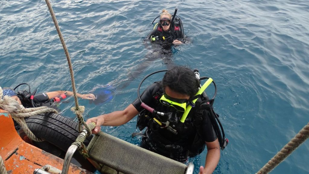 Sayak coming out of the water, climbing the stairs to the boat after a dive with diving gear on in Koh Tao, Thailand