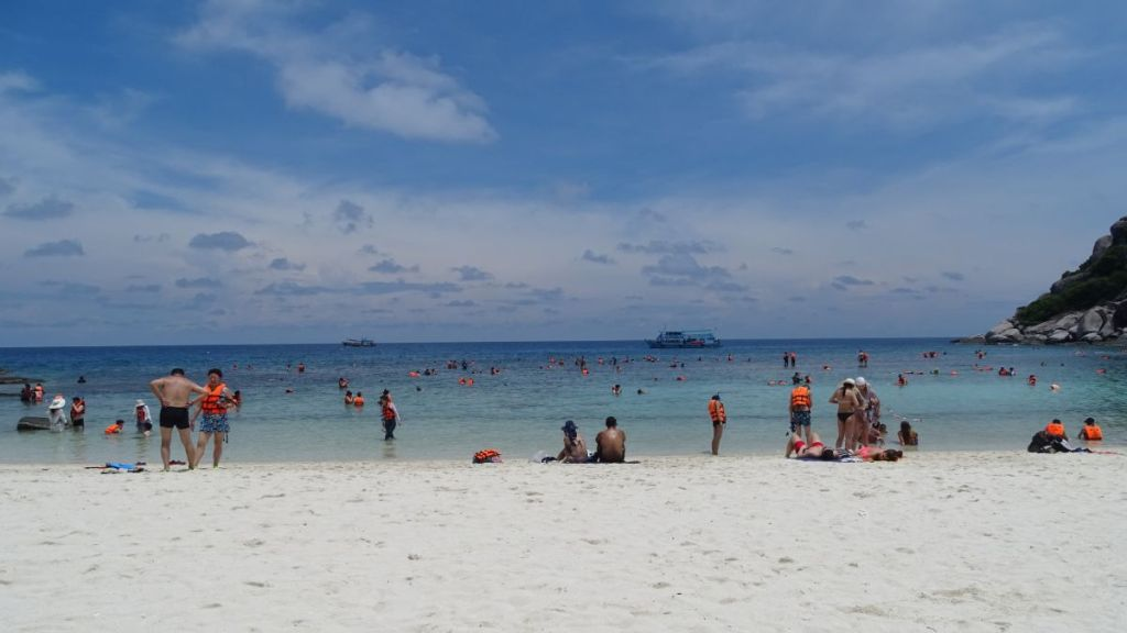 Crowded beach full of snorkelers wearing life jackets on Koh Nang Yuan island, Thailand