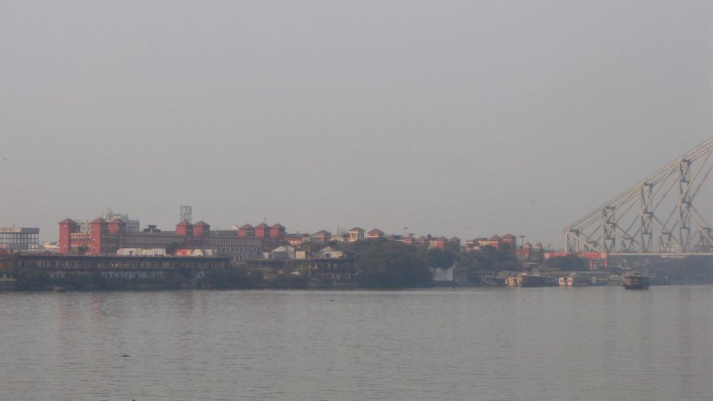 Enormous red building of the Howrah railway station in Kolkata seen from the other bank of Ganges