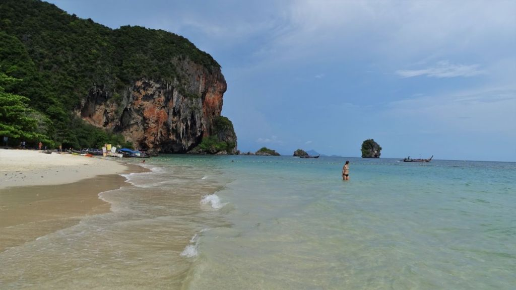 Weronika standing in shallow water of Phra Nang beach with karst formation in the background