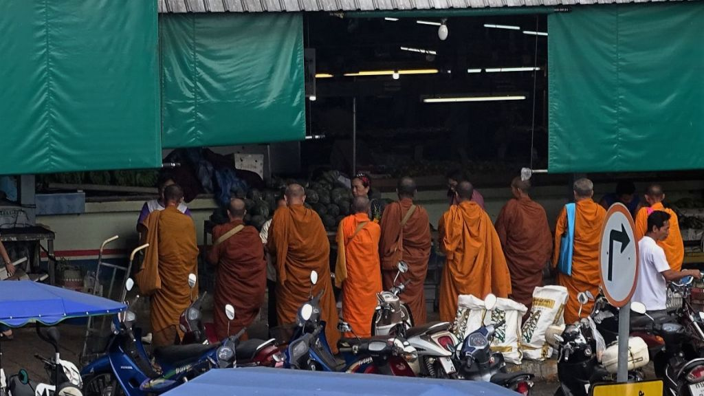 Nine monks wearing orange, maroon robes are standing front of Krabi market for alms