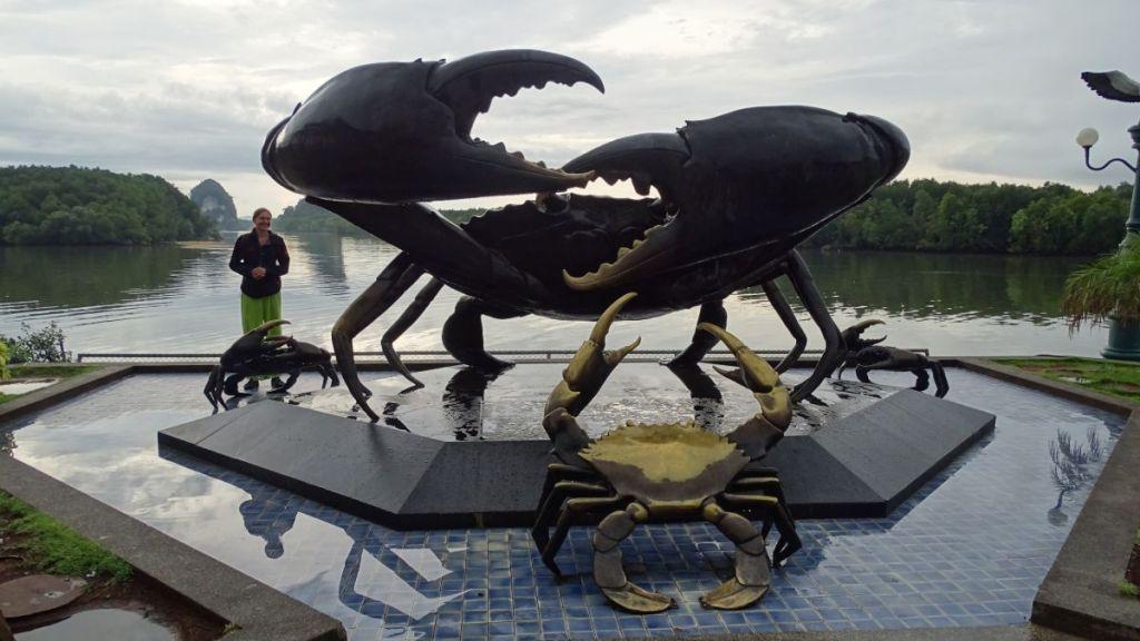 Weronika standing next to a statue of a crab, having Krabi river behind