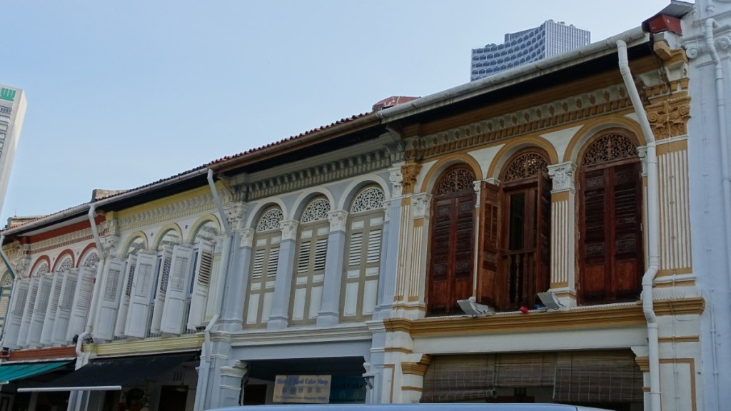 A row of Sino-Portuguese-styled shophouses with columns and wooden shutters in Singapore's downtown
