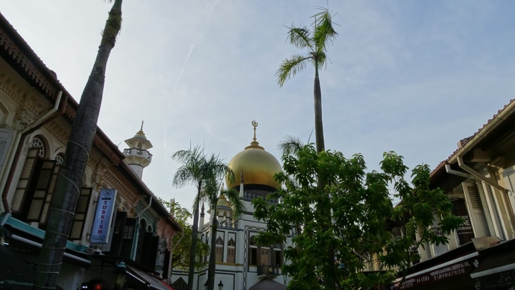 A large, golden dome of the Sulta's Mosque and the upper floors of the colonial style buildings in Kampong Glam.