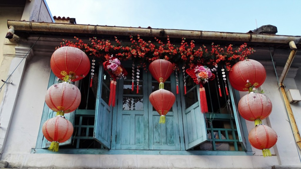 Wooden window shutters adorned with red lanterns in Singapore's China Town