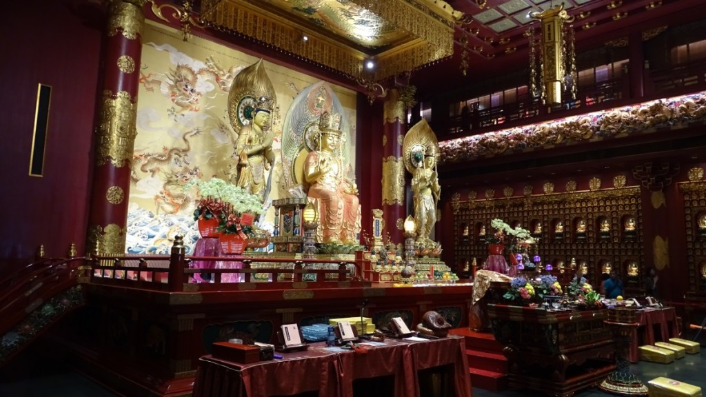 The bordo- golden interior of the Temple of the Tooth Relic in Singapore with an altar of Buddha and the golden background of flying dragons.
