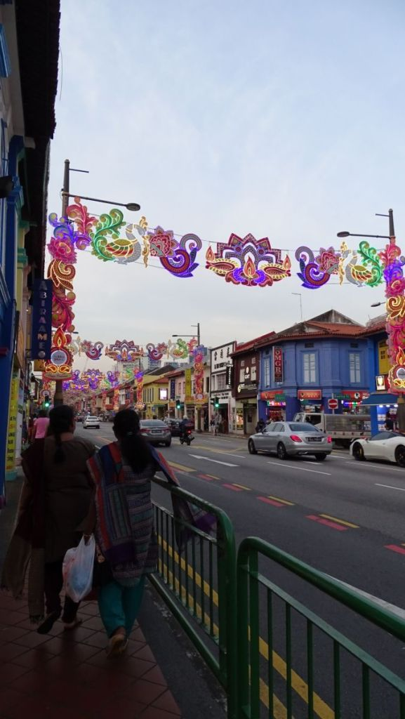 Street in Singapore's Little India with ethnic style colourful decorations across the street and ladies in Indian kurta pajamas walking