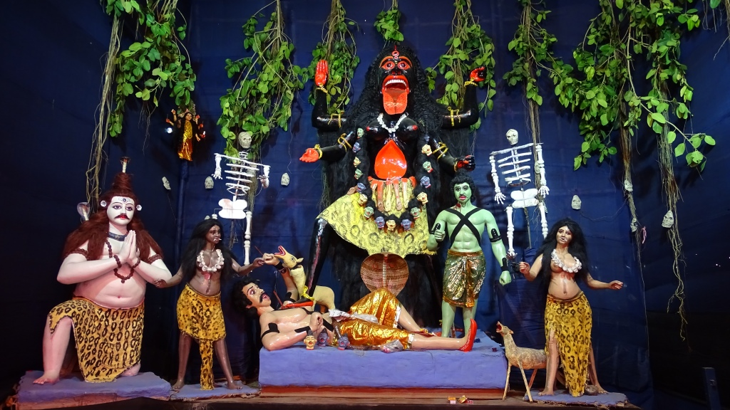 A temporary altar for Kali Puja featuring scary figure of black goddess with huge red tongue steppig on a man, skeletons, and other deities below her.