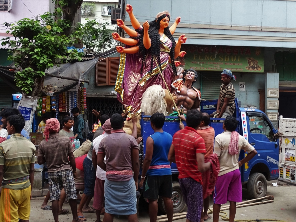 Porters loading a 2 meters tall figure of goddess Durga ona small truck in Kumartuli district just before Durga Puja celebrations