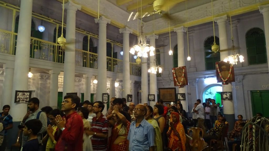 A small gathering of people, some in prayer, inside the historic, grand interior Chatu Babu Latu Babu Rajbari mansion in Kolkata during Durga Puja