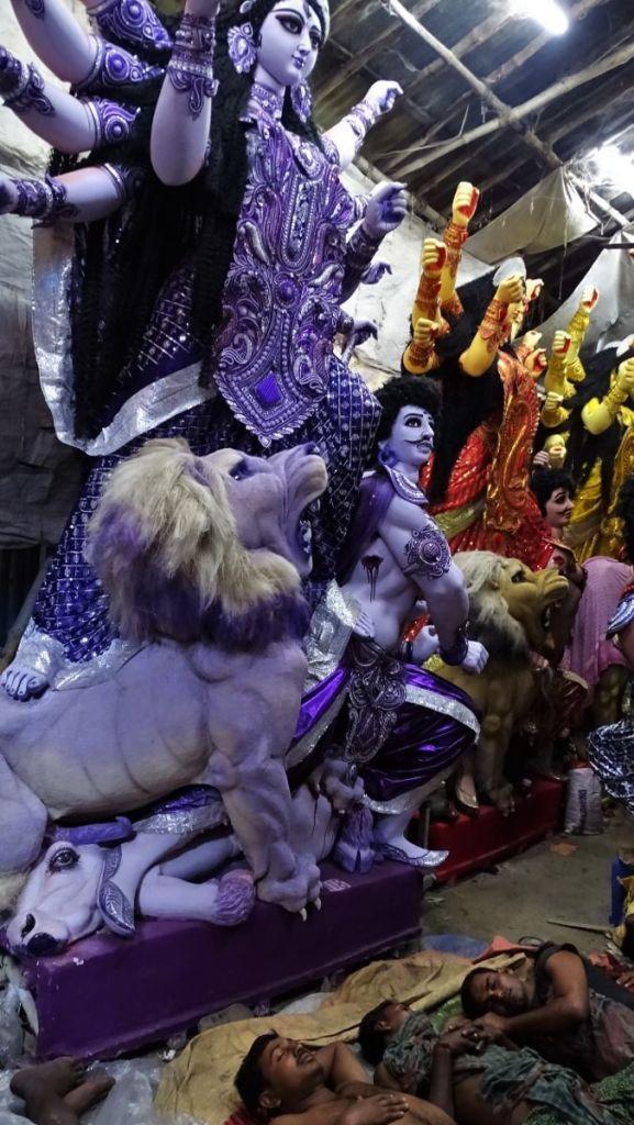 Craftsmen sleeping under the finished idols of Durga a few days before the Durga Puja celebrations in Kolkata