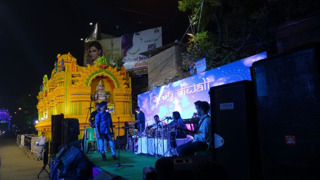 A golden, temporary altar set up on the street next to a small stage where a concert takes place to celebrate Diwali in Kolkata