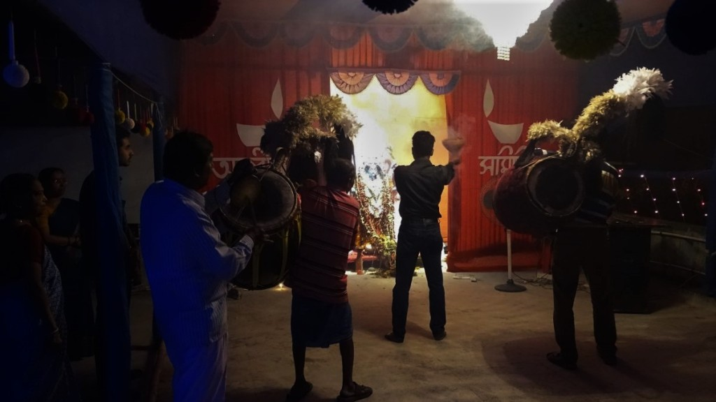 Family celebrations of Kali Puja on the roof: man holds smoking clay pot in front of the idol while the drummers play