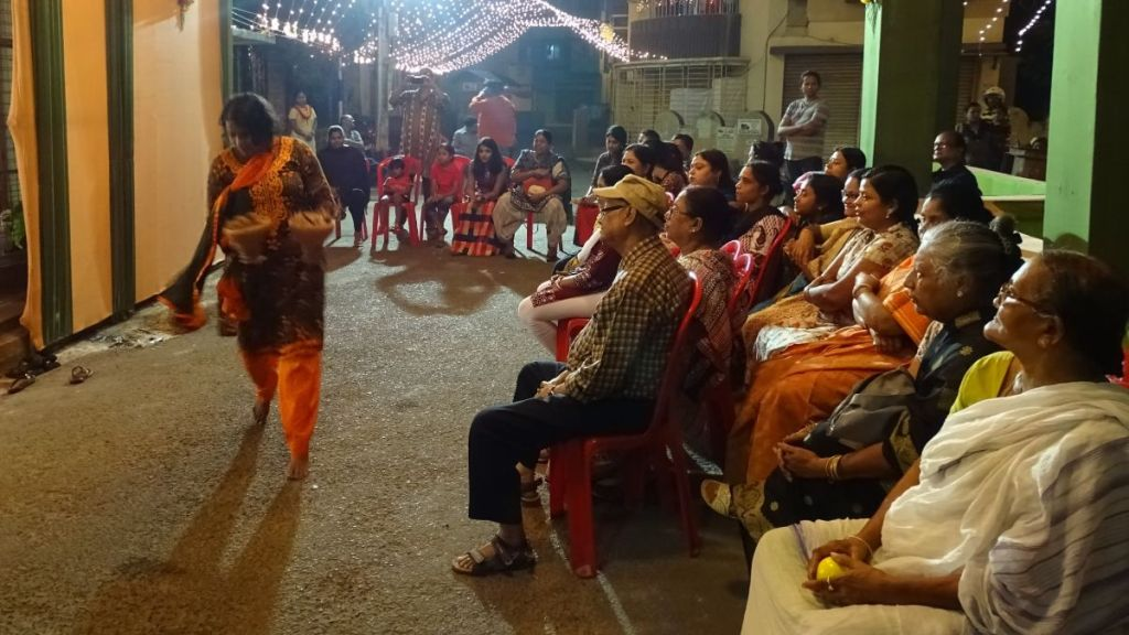 A woman dances dhunuchi with two clay pots in her hands. The people from the neighbourhood, sitting on plastic chairs set up on the street watch by.