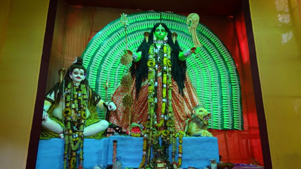 A green-colour Kali with a lion at her side and thousand hands represented on a semicircular background behind her. A Kali Puja at Chetla in Kolkata.