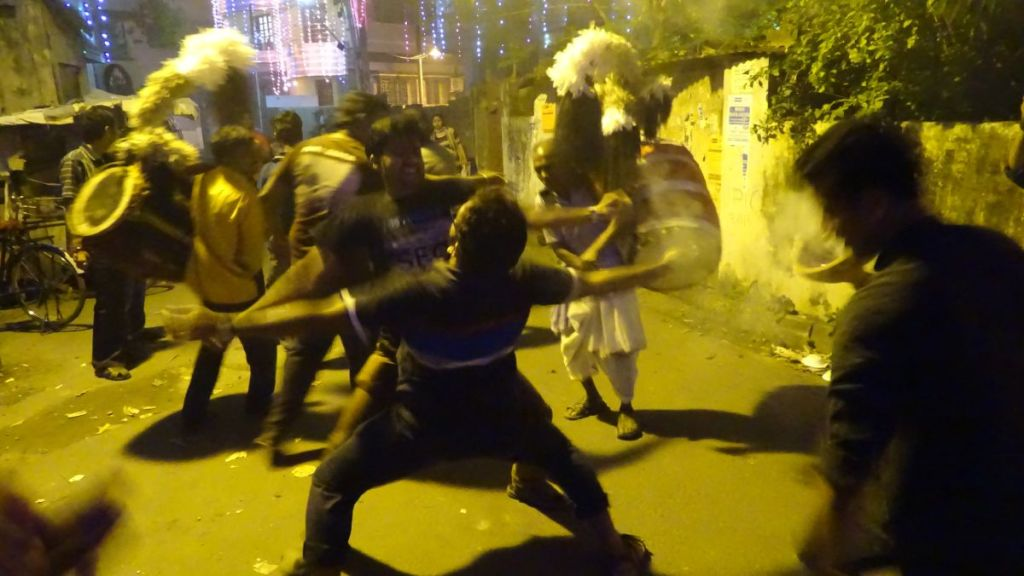 Drummers playing dhak and men dancing with each other in an immersion procession during Kali Puja in Kolkata