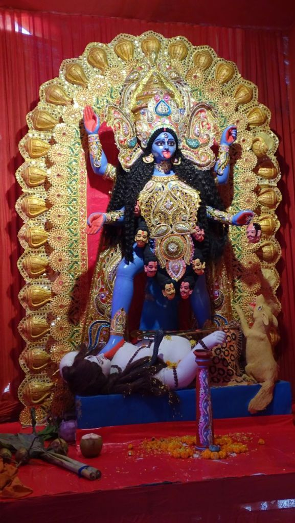 An idol of blue-coloured Kali wearing a skull-garland, holding in one of her four hands a head and stepping on her husband Siva