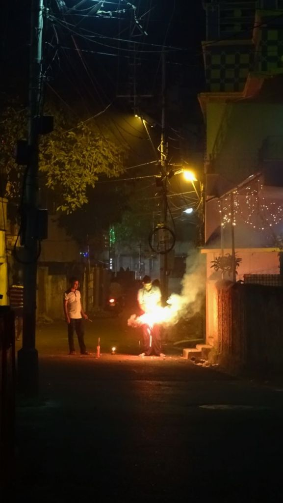 Two young men lit a firecracker on a small lane in Kolkata to celebrate Kali Puja