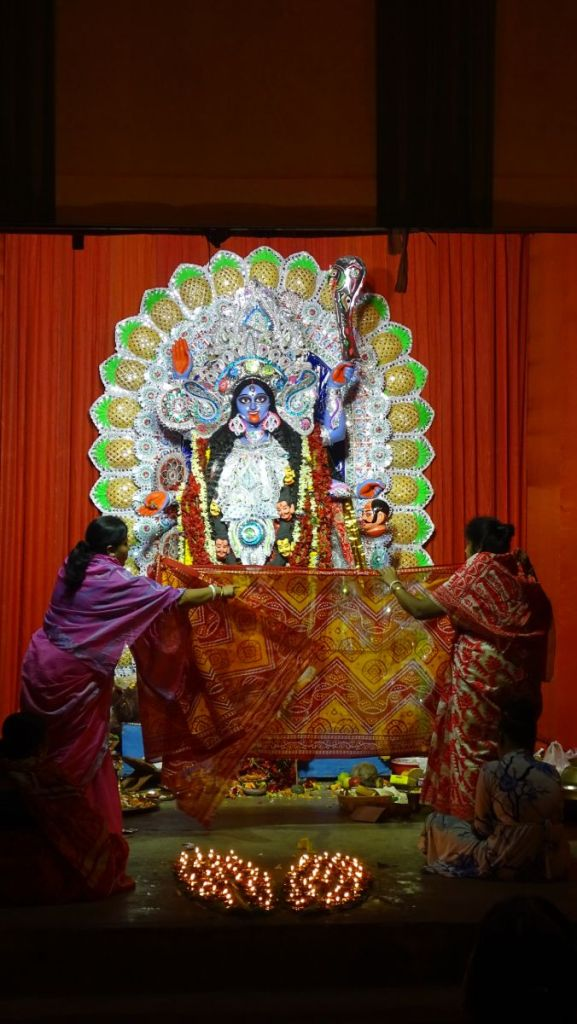 Kali Puja ritual: two women cover the idol of Kali goddess with a sari, two banana leaves filled with lit oil lamps in front of them