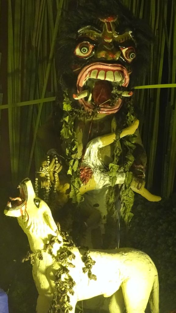 Kali Puja decorations: a scary, monstrous dakini demon with massive teeth eats a human, a howling jackal beneath her