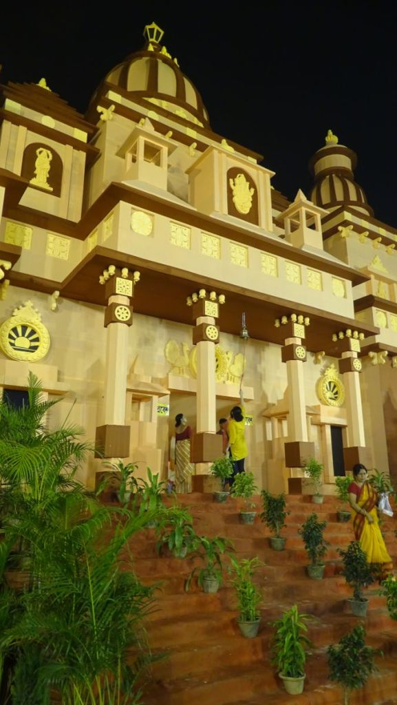 A large, temple-shaped Kali Puja pandal in Parnasree district of Kolkata visited at night by devotees