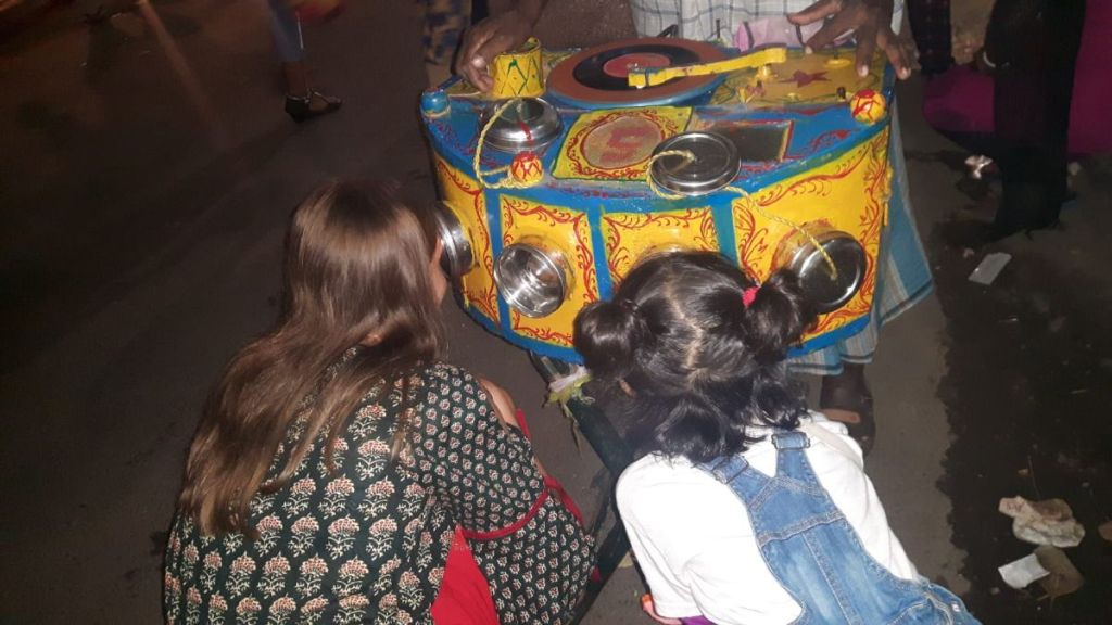 Weronika and a little girl look through the bioscope- a box with magnifying glass held by a street vendor at a fair set for Kali Puja in Kolkata