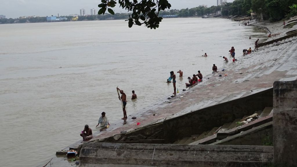 People washing their clothes and having a bath on the ghats, steps leading to Hooghly river in Kolkata