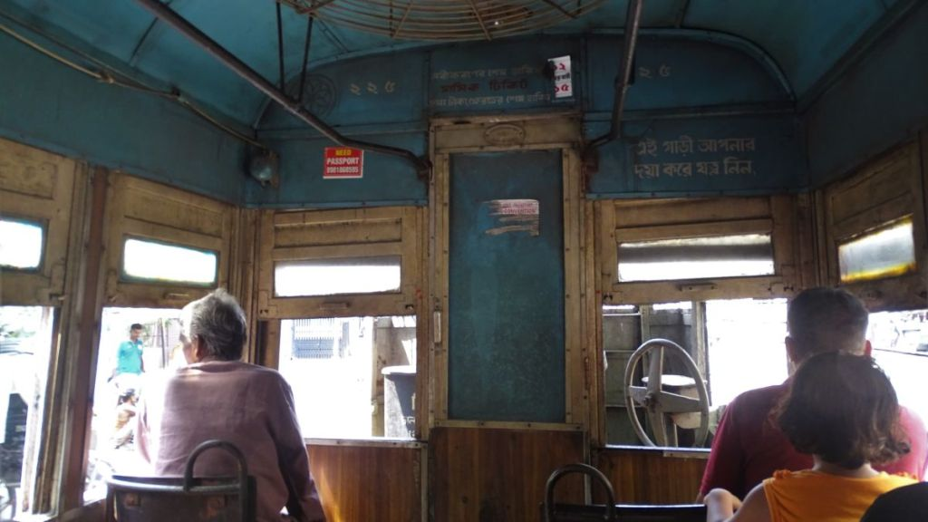 The interior of the ancient tram in Kolkata with wooden seats and a steering wheel of the driver visible