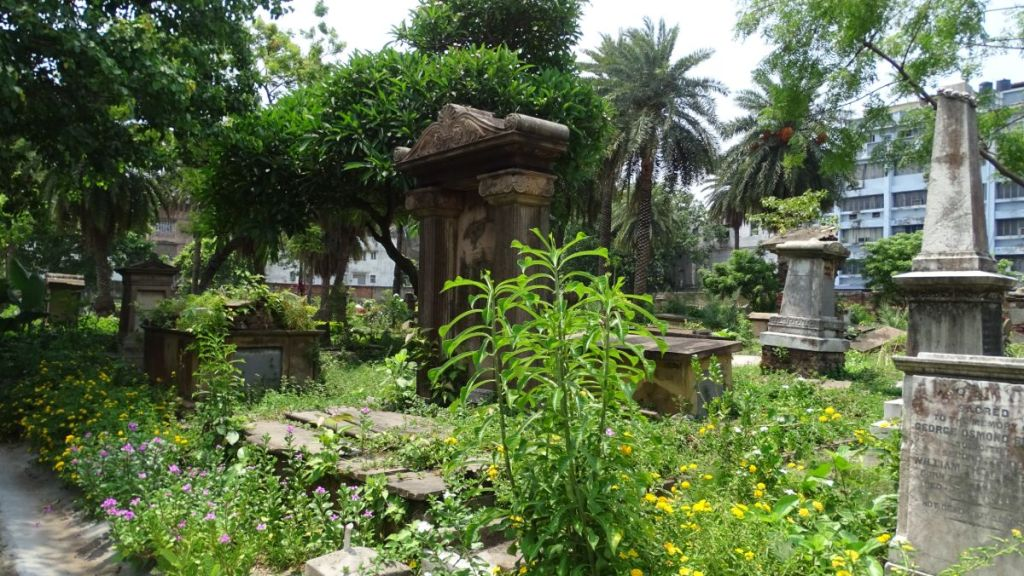 Modest, old tombstones set among verdant greenery and flowers at the Scottish Cemetery in Kolkata