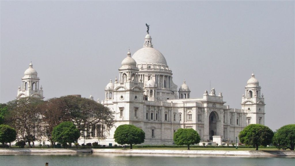 Victoria Memorial in Kolkata: a white marble building with four towers and a large dome seen across a pond.