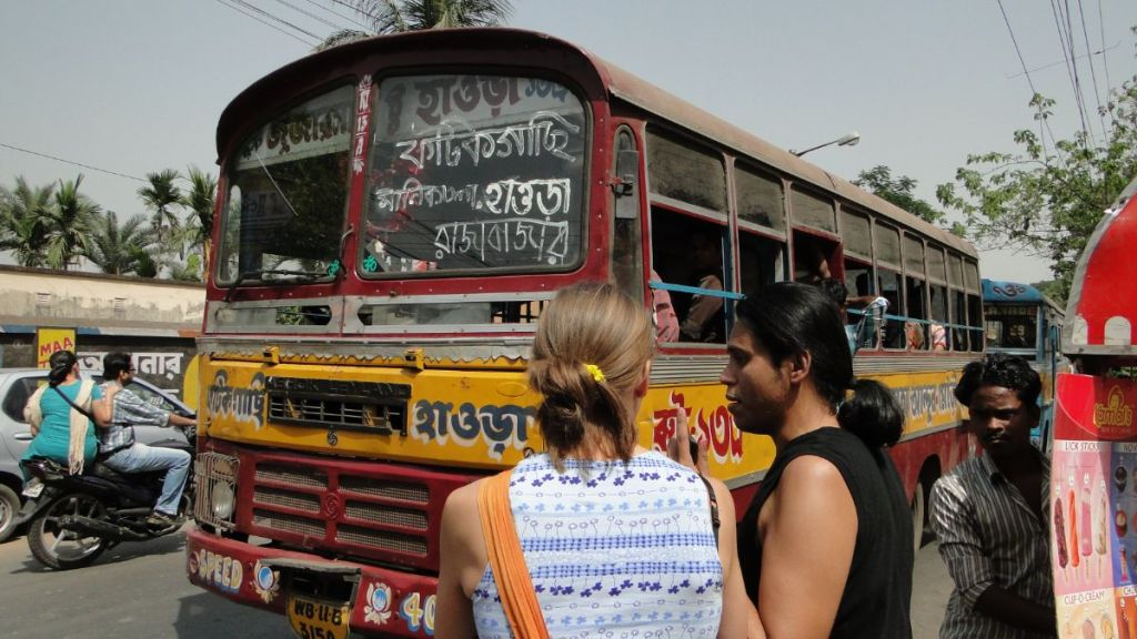 Sayak and Weronika standing in front of a red, battered bus with Bengali script all over in Kolkata