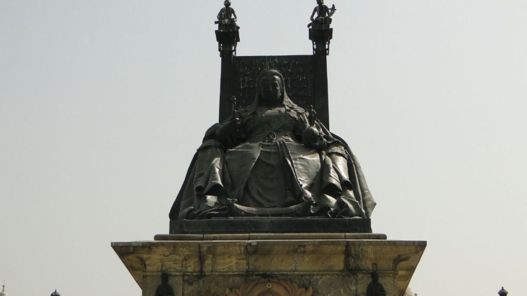 A seated statue of Queen Victoria in front of the Victoria Memorial in Kolkata, India