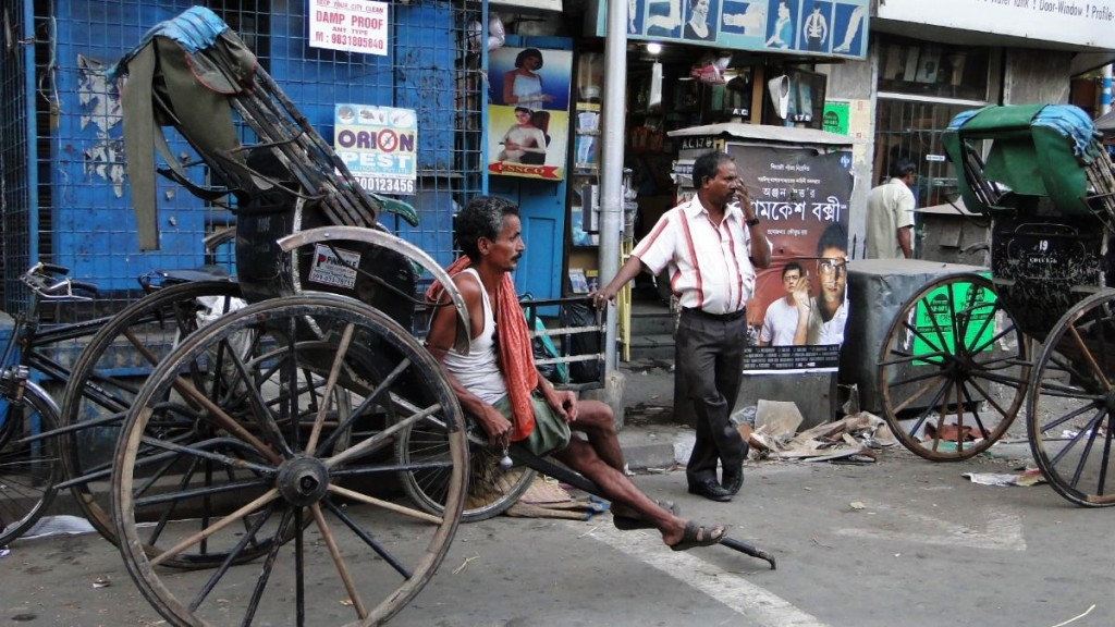 A lean, muscular rickshaw puller sitting on his rickhaw waiting for a customer in north Kolkata