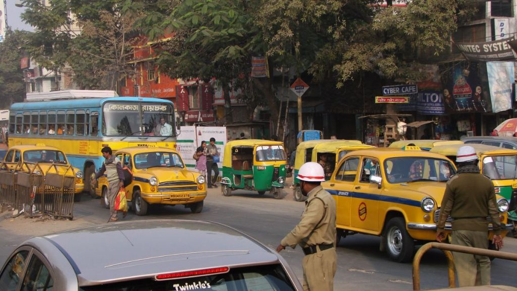 A street in Kolkata full of old-fashioned yellow taxis, yellow and green autorickhaws and a blue and yellow old bus. Two pollicemen control the traffic