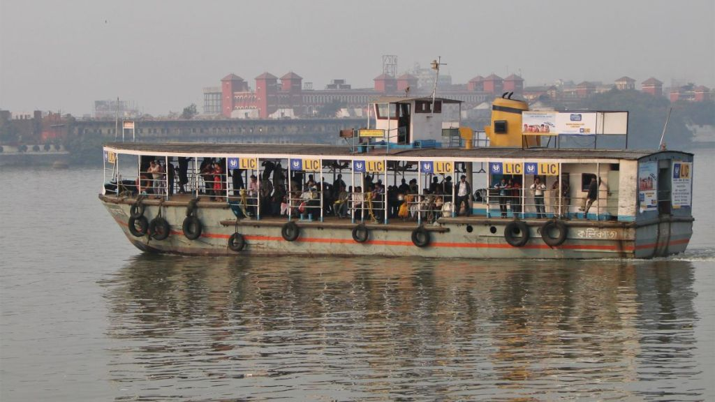 A large pedestrian ferry half-filled with people on the Hooghly river in Kolkata, the huge Howrah railway station visible in the background