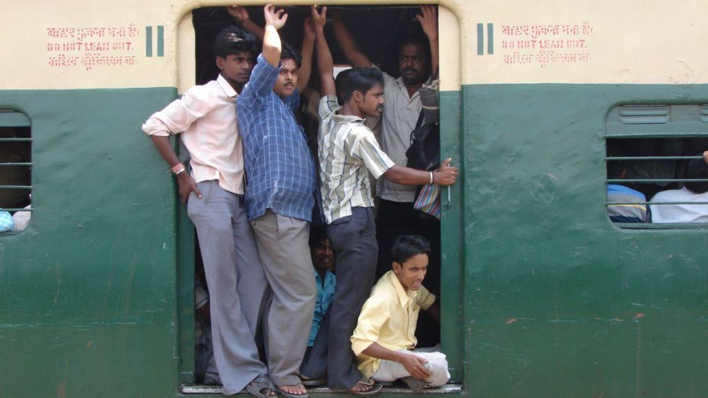 The doors of the male compartment of a suburban train in Kolkata with man hanging outside the train and sitting on the ground