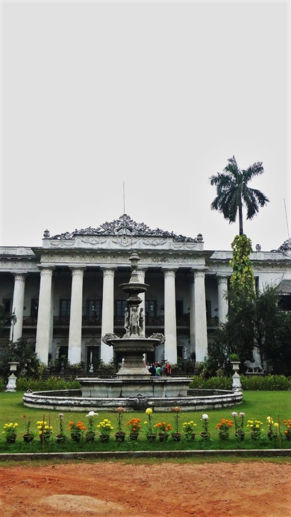 A white classicist fountain and the classicist facade of the Marble Palace in Kolkata