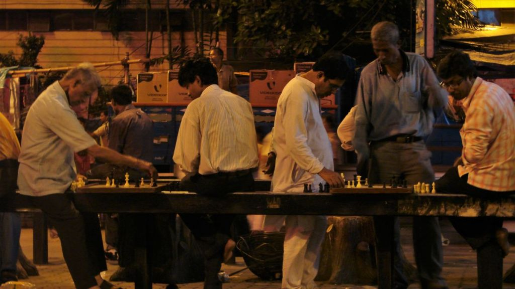 Groups of middle- aged men play chess on the road barrier in Kolkata