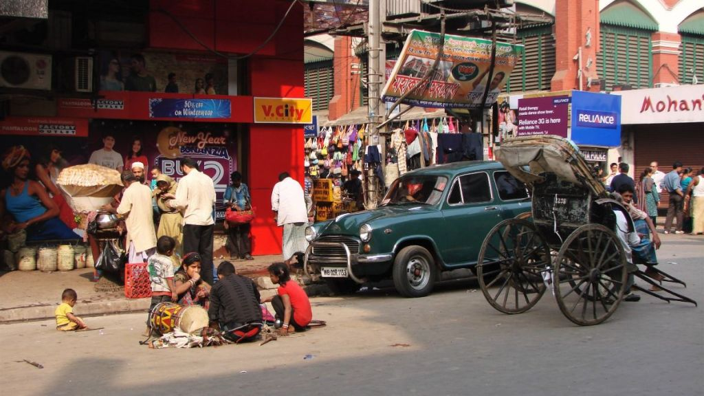 Street in north Kolkata: a family of beggars squatting on the asphalt, a hand-pulled rickshaw wallah waiting for a passenger and people eating from a street stall