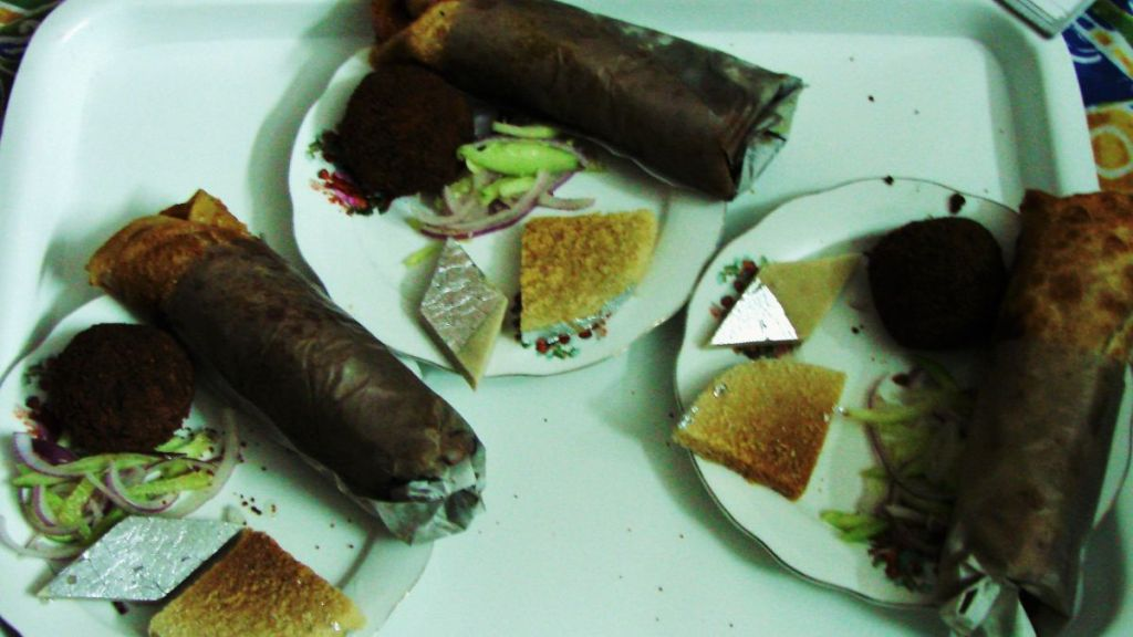 Plates with Bengali rolls (pancakes wrapped with filling), chops (breaded deep fried snacks) and milk sweets