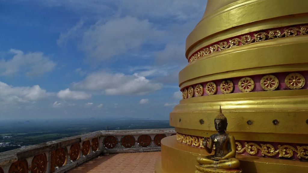 A small sitting Buddha in front of a giant stupa at the top of tiger cave temple, krabi
