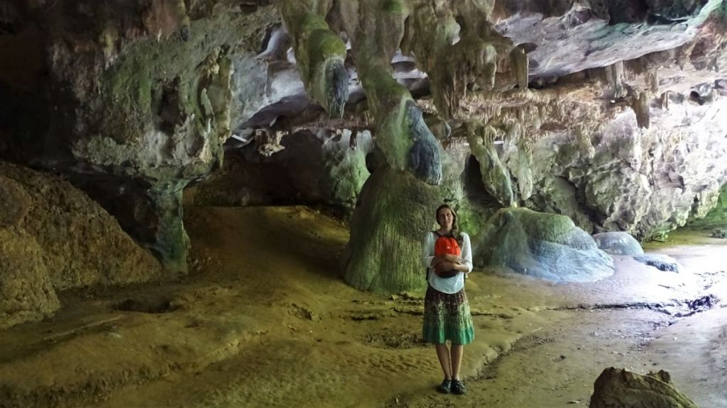 Weronika standing inside a half-open cave with rock formations in the background on the base of Tiger cave, Krabi
