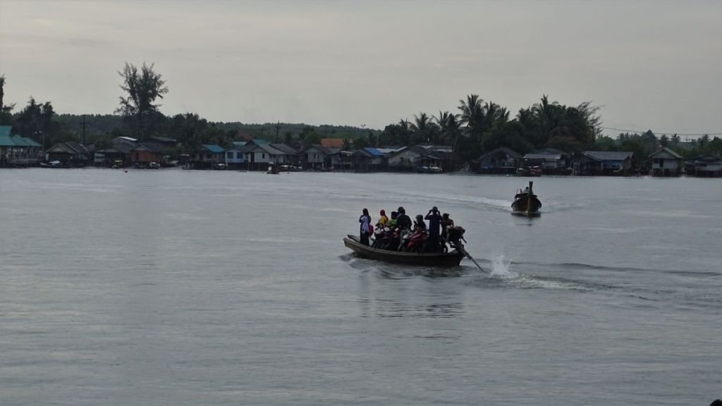 A small boat with people and scooters in Krabi river with houses in Ko Klang, Krabi in the background