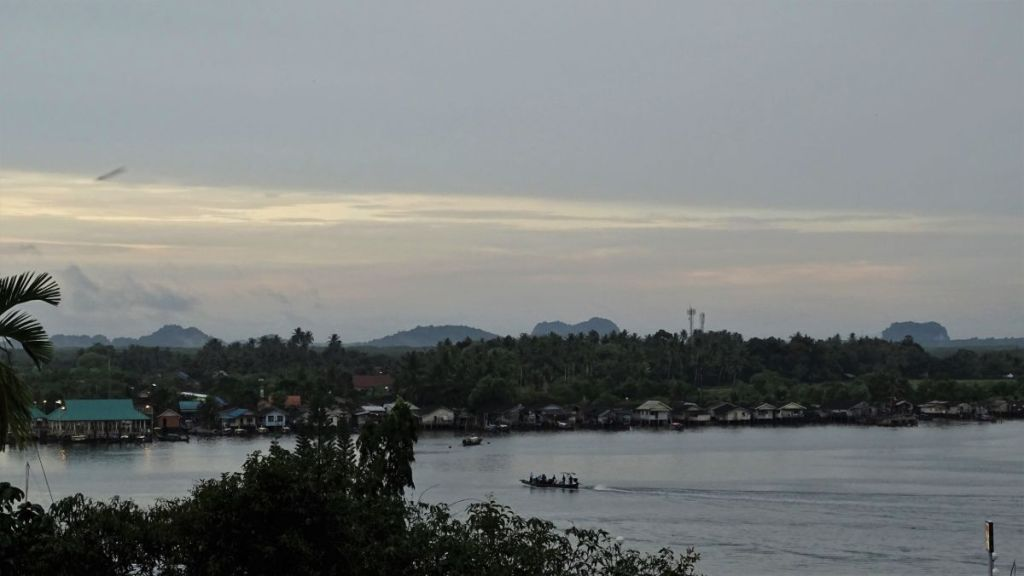 Ko Klang island with few karst formations in the background and a boat in Krabi river from a vantage point,Krabi