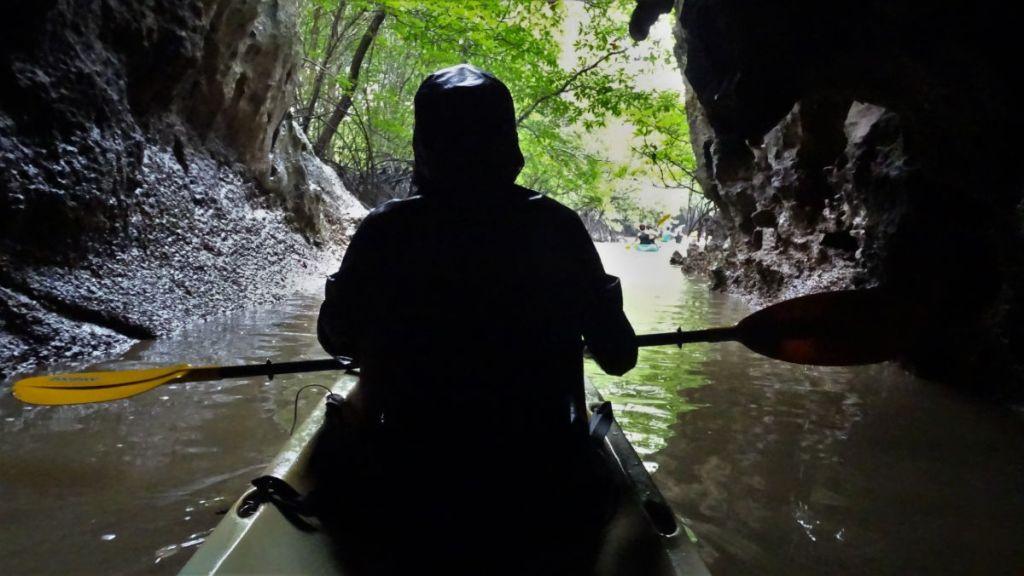 Weronika is kayaking through a cave with waterproof jacket on, in Krabi, Thailand